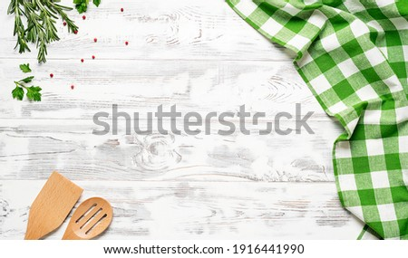 White wooden table covered with green tablecloth and cooking utensils. View from top. Empty tablecloth for product montage. Free space for your text Royalty-Free Stock Photo #1916441990