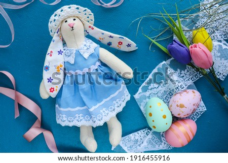 easter greeting card for kids. flowers, willow twigs, easter bunny figurine, easter eggs and space for text