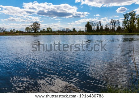 Landscape of Odra river with grass and bushes in front of at cloudy sunny day Royalty-Free Stock Photo #1916480786