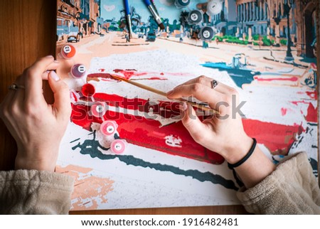 Painting for beginners, a woman draws a picture by numbers with acrylic paints on canvas artist draws a picture, painting a picture with a brush, a girl draws a picture, self-isolation, home hobby
