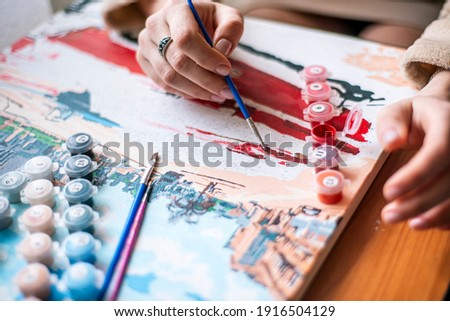 painting by numbers, artist draws a picture, painting a picture with a brush, a girl draws a picture, self-isolation, home hobby, creativity at home, bright colors, positive mood, relax retreat