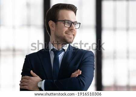Smiling young businessman in suit and glasses look in window distance thinking or planning career success. Happy Caucasian male director or CEO thinking visualizing in office. Business vision concept. Royalty-Free Stock Photo #1916510306