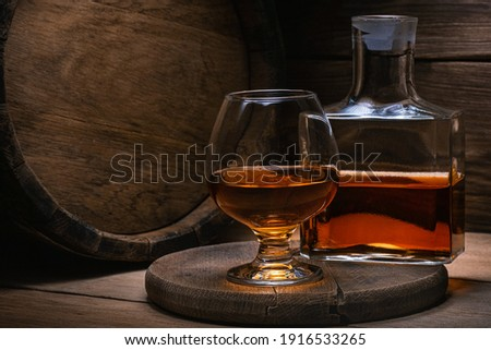 Glass cognac, bottle of cognac and an old oak barrel of cognac with blurred background in the light rays. Table on a wooden stand there is decanter of skate and glass of cognac against. Royalty-Free Stock Photo #1916533265