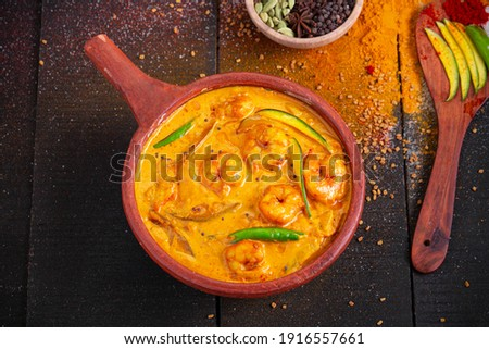 Prawn mango curry,kerala traditional dish made using raw mango and  arranged in an earthen ware with black textured background