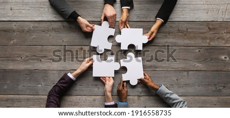 Business teamwork with white puzzle of four pieces cooperation unity concept Royalty-Free Stock Photo #1916558735
