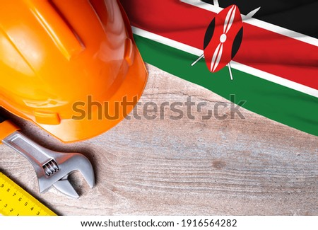 Kenya flag with different construction tools on wood background, with copy space for text. Happy Labor day concept. Royalty-Free Stock Photo #1916564282