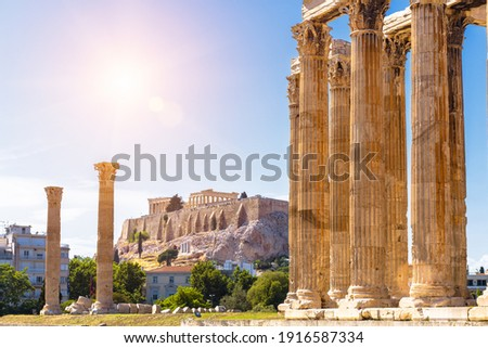 Zeus temple overlooking Acropolis, Athens, Greece. These are famous landmarks of Athens. Sunny view of Ancient Greek ruins, great columns of classical building in Athens city center. Travel concept. Royalty-Free Stock Photo #1916587334
