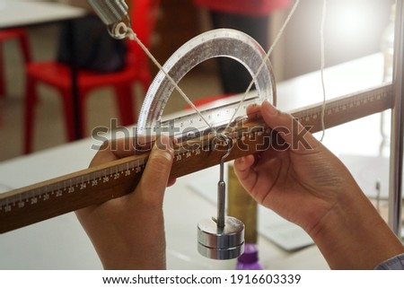 A physics experiment on equilibrium of three forces, angles measured by the protractor. Scientific practice concept. Scientific experiment.