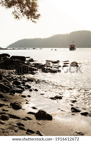 Boat in the sea against the background of misty mountains with rocks on the beach in the foreground at bright sunset with rays of seeing sun in Turkey, Phaselis Royalty-Free Stock Photo #1916612672