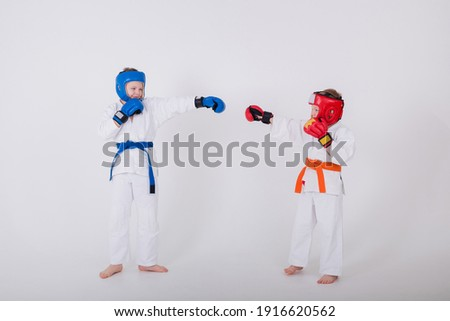 two boys in a white kimono and wearing a helmet and gloves compete on a white background with a place for text Royalty-Free Stock Photo #1916620562