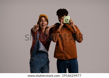 Photo of cute couple farmers take a photo on polaroid and looks happy together . White woman wears denim overall, black man shirt isolated grey color background