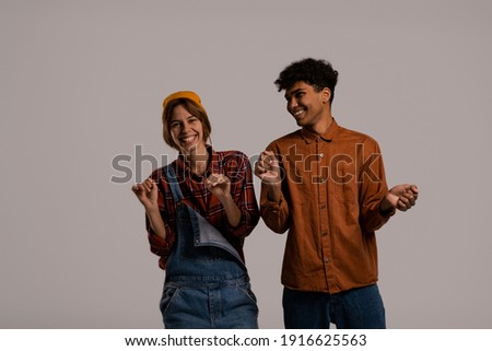 Photo of cute couple farmers smile and dance together, have fun. White woman wears denim overall, black man shirt isolated grey color background