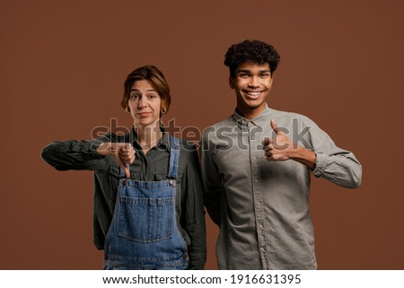 Photo of cute couple farmers. Female farmer shows thumb down but male shows up. Woman wears denim overalls, man wears t-shirt, isolated brown color background