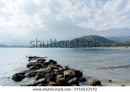 stone pier on a sandy beach in the sea against the background of green misty hills covered with forests under a blue sky with white clouds. Phaselis beach. Turkey national natural landmarks Royalty-Free Stock Photo #1916633192