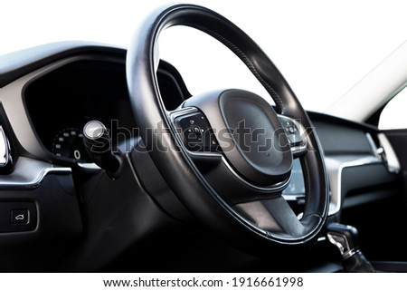 Black luxury modern car Interior. Steering wheel, shift lever and dashboard. Detail of modern car interior. Automatic gear stick. Part of leather seats with stitching in expensive car Royalty-Free Stock Photo #1916661998