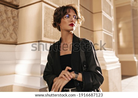 Trendy girl with wavy hairstyle and red lips posing outside. Brunette woman in dark jacket and glasses looks away outdoors.. Royalty-Free Stock Photo #1916687123