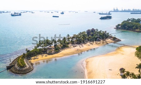 Aerial picture of Palawan Beach in Sentosa Island Singapore. View from beach to sea. Sunny warm day. Turquoise water and green trees. Anchored ships in the horizon.