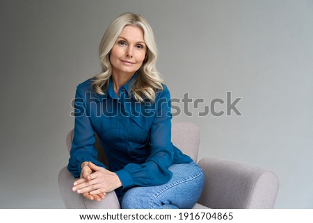 Middle aged female psychotherapist, counselor sitting in chair alone in office looking at camera. Sophisticated elegant mature 50s woman of mid age with blond hair posing indoors, portrait. Royalty-Free Stock Photo #1916704865