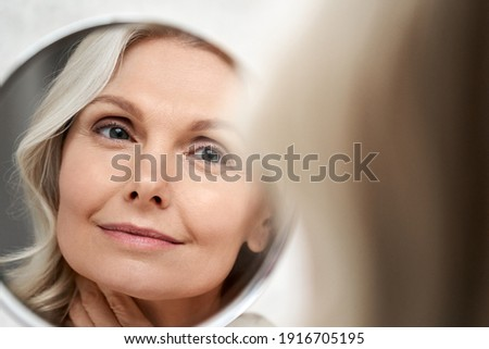 Happy 50s middle aged woman model touching face skin looking in mirror reflection. Smiling mature old lady pampering, healthy moisturized skin care, aging beauty, skincare treatment cosmetics concept. Royalty-Free Stock Photo #1916705195