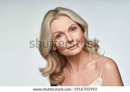 Beautiful 50s middle aged mature woman looking at camera isolated on white. Mature old lady close up portrait. Anti age healthy face skin care beauty, older skincare cosmetics, and cosmetology concept Royalty-Free Stock Photo #1916705993