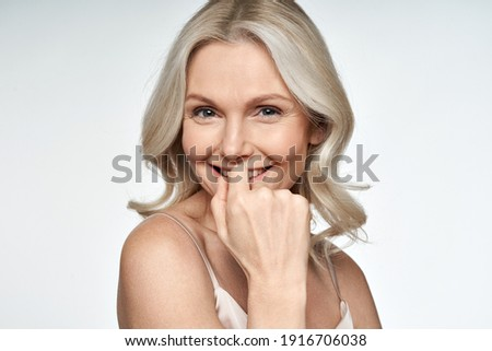 Happy smiling attractive 50s middle aged blonde woman looking at camera advertising antiage face skin and aging hair care treatment and cosmetics isolated on white background. Close up portrait. Royalty-Free Stock Photo #1916706038