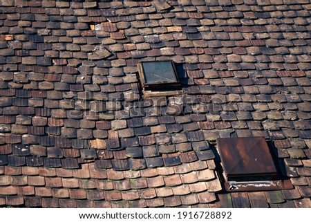 Picture of an old, wheathered roof, awaiting renovation, with ceramic roof tiles in bad condition and two skylight with broken glass; color photo.