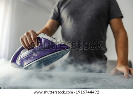 Powerful professional photo effect of water vapor from the hot iron. A modern lifestyle concept, a man who irons clothes at home Royalty-Free Stock Photo #1916744492