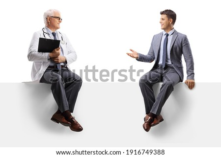 Professional man sitting on a panel and talking to a mature doctor isolated on white background Royalty-Free Stock Photo #1916749388
