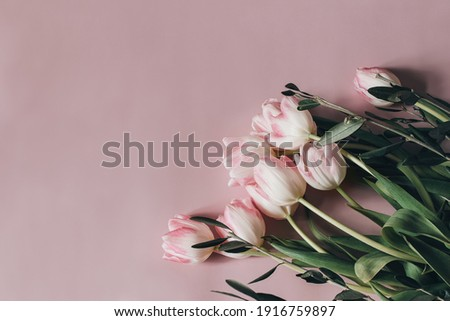 Natural styled stock photo. Feminine Easter, spring composition with tulips on pink table, wall background. Floral frame, border. Flat lay, top view. Vertical picture for blog, web banner. Royalty-Free Stock Photo #1916759897