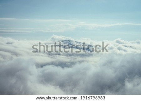 Wonderful minimalist landscape with mountain top above dense low clouds. Mountain vertex floats in thick clouds. Scenic minimalism with mountain peak above cloudy sky. Beautiful summit in cloudiness. Royalty-Free Stock Photo #1916796983