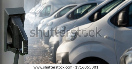 Electric vehicles charging station on a background of a row of vans. Concept Royalty-Free Stock Photo #1916855381