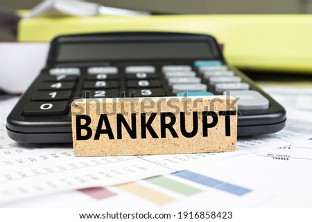 The word bankrupt is written on a wooden cube that stands on a financial document on a blurred background of a black calculator. Business and financial concept Royalty-Free Stock Photo #1916858423