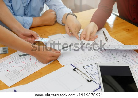 Graphic designers work together with UX UI designer planning application template layout framework for mobile phone computer mobile Royalty-Free Stock Photo #1916870621