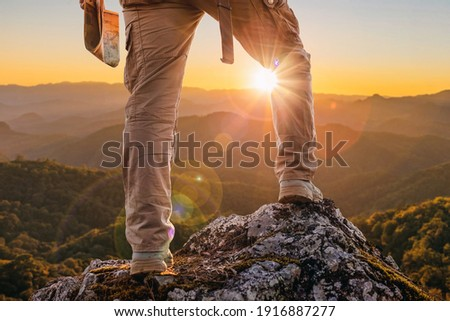 Hiker standing on top mountain sunset background. Hiker men's hiking living healthy active lifestyle. Royalty-Free Stock Photo #1916887277
