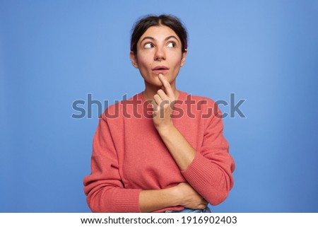 Picture of enthusiastic thoughtful young Caucasian woman with nose ring looking up with curious pensive facial expression, holding finger at her chin, thinking how to realize ambitious plan