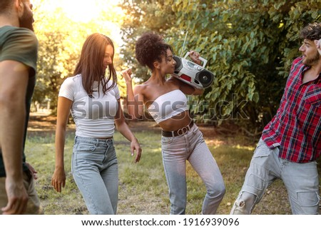 Gathering of multiracial friends dancing happy in the nature, african descent woman holding a boombox