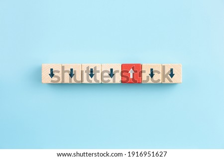 Red wooden block with arrow facing individual pointing in the different way on blue background, Business icon for innovative solution,Unique, think different and individual concept.