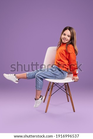 Full body side view of smiling little girl in orange sweatshirt and jeans with white sneakers sitting on chair in studio against violet background Royalty-Free Stock Photo #1916996537