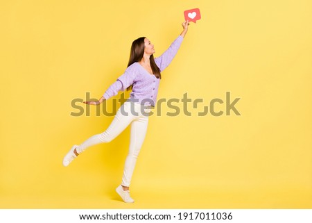 Full length body size view of pretty cheerful girl jumping holding paper red card like isolated over bright yellow color background