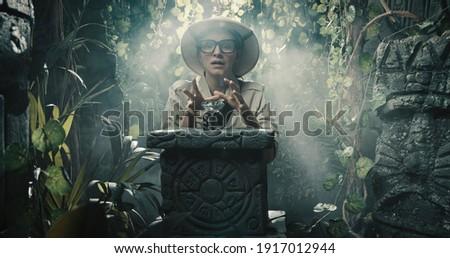 Happy explorer finding a precious treasure in the tropical jungle, adventure and fantasy concept Royalty-Free Stock Photo #1917012944