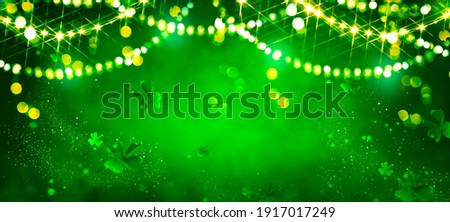 St. Patrick's Day abstract green background decorated with shamrock leaves. Patrick Day pub party celebrating. Abstract Border art design magic backdrop. Widescreen clovers on black with copy space Royalty-Free Stock Photo #1917017249