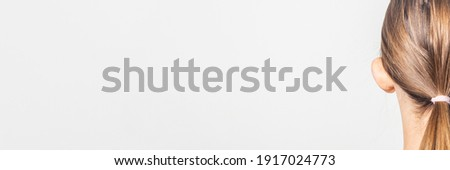 Lop-eared female ear, rear view on a light background. Auricle defect. Banner Royalty-Free Stock Photo #1917024773