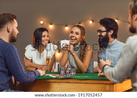 Happy young woman showing two aces while playing poker while sitting at a game table with her friends. Concept of themed celebrations of birthdays or corporate events in a casino or at home. Royalty-Free Stock Photo #1917052457