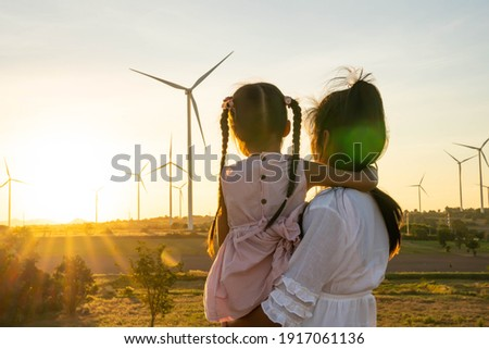 Wind turbines are alternative electricity sources, the concept of sustainable resources, People in the community with wind generators turbines, Renewable energy. Royalty-Free Stock Photo #1917061136