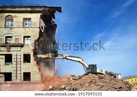 excavator demolishing a brick building. Machinery Demolishing Building Royalty-Free Stock Photo #1917095531