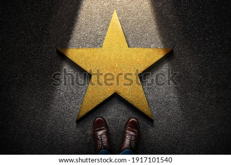 Success in Business or Personal Talent Concept. Top View of Business Person in Working Shoes Standing in front of a Golden Star. Light Shining on the Dark Cement Floor Royalty-Free Stock Photo #1917101540