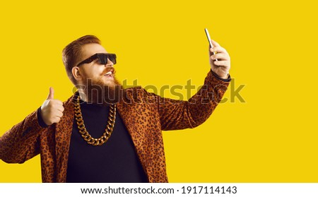 Funny cheerful red haired bearded overweight man hipster in leopard jacket, golden chain and sunglasses making selfie on smartphone over yellow background. Funny style or male concept