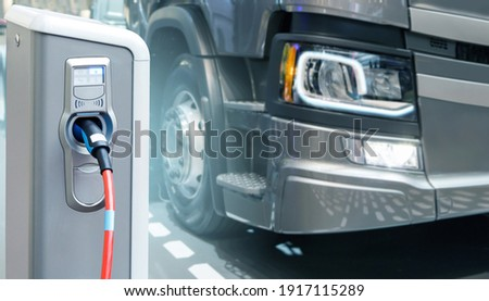 Electric vehicles charging station on a background of a truck. Concept Royalty-Free Stock Photo #1917115289