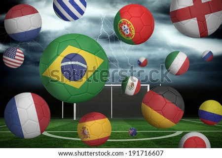 Footballs in various flag colours against football pitch under stormy sky #191716607