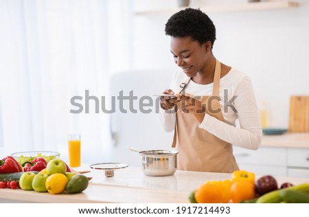 Food Blogging. African Lady Taking Photo Of Prepared Dinner In Saucepan On Phone Cooking In Modern Kitchen At Home. Nutrition Blog, Household Leisure Concept. Weight Loss Application